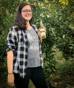 Vale Cider bottle being held by young woman in orchard