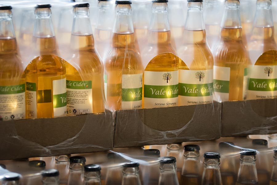 Cases of Serious Scrumpy Vale Cider with sunlight shining through them