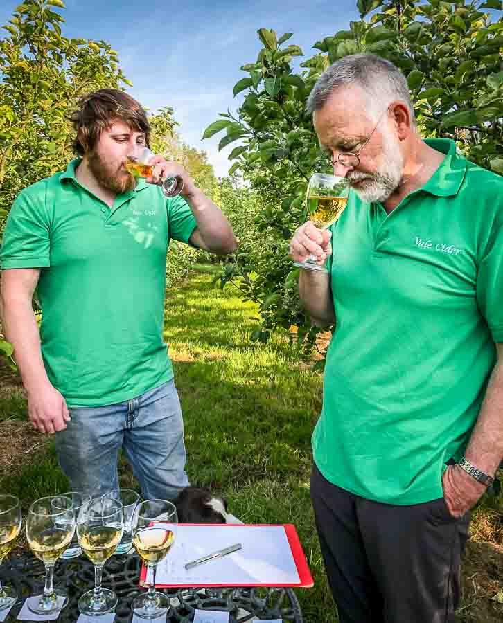 Two men tasting cider in an orchard