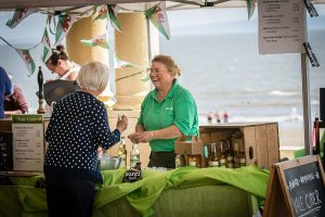 Woman serving customer at Vale Cider stall on seafront