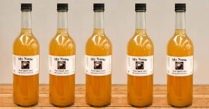 Row of bottles of apple juice with bespoke labels