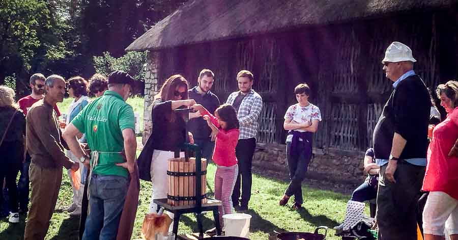 apple pressing demonstration outside an old barn