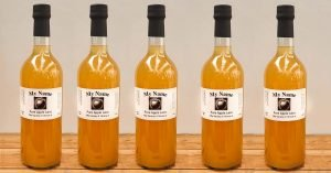 row of bottled apple juice with labels and capsules