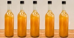 unlabelled bottles of apple juice